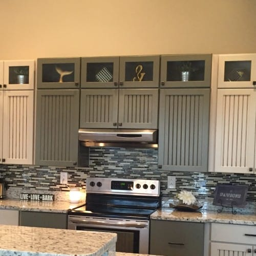 """In the kitchen, glass topper cabinets are filled with accents of gold and silver unusual objects, or """"weirds."""""""