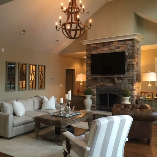 In the living room, the oversized sofa is replaced with a silvery three seater, and the stone fireplace is still an intricate design focus.